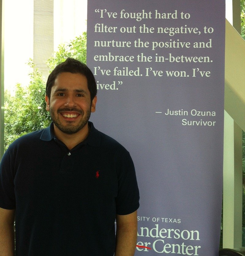 Image of Justin Ozuna standing next to a banner at MD Anderson
