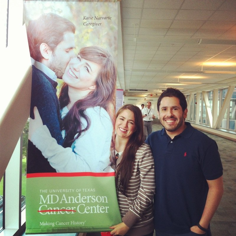 Image of Justin and Katie Ozuna standing next to a banner with their photo on it at MD Anderson in Houston, Texas